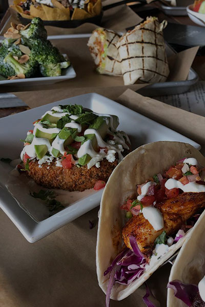 A Quiet Pint table filled with a variety of menu items. Including tacos, a wrap, broccoli, nachos, and more.
