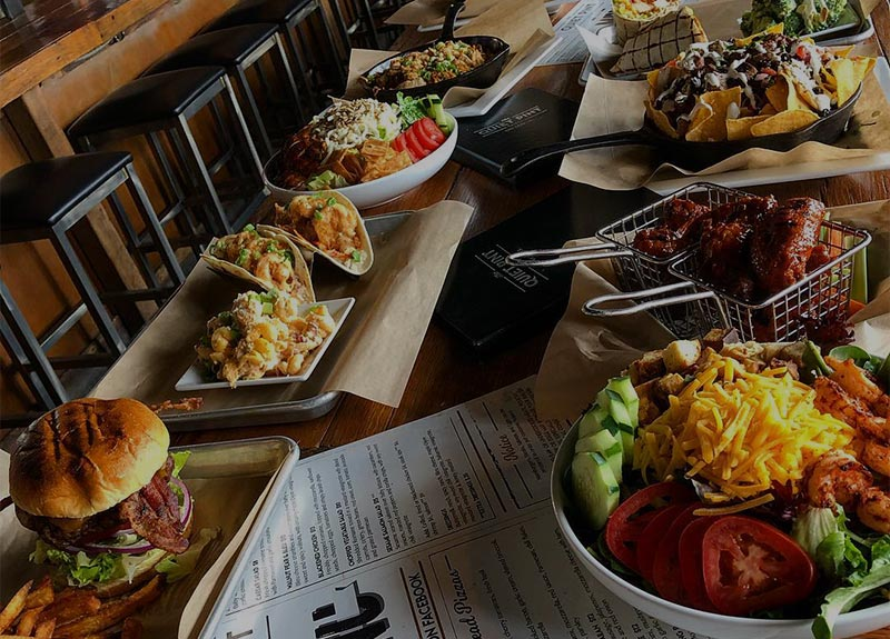 A Quiet Pint table filled with a variety of menu items and menus. Food includes: salad, bacon burger, tacos, wings, nachos, wraps, and more.